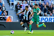 Yoshinori Muto (#13) of Newcastle United heads towards goal pursued by Craig Cathcart (#15) of Watford during the Premier League match between Newcastle United and Watford at St. James's Park, Newcastle, England on 31 August 2019.