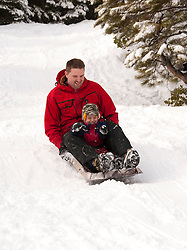 California, Lake Tahoe: Child and father enjoy snow play with sled at North Lake Tahoe Regional Park.  Photo copyright Lee Foster.  Photo # cataho107635