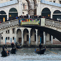 VENICE, ITALY - FEBRUARY 18:  Gondolas sail inder Rialto Bridge where a sign invites to Venice Carnival 2012 on February 18, 2012 in Venice, Italy.  The annual festival, which lasts nearly three weeks, will see the streets and canals of Venice filled with people wearing highly-decorative and imaginative carnival costumes and masks.  (Photo by Marco Secchi/Getty Images)