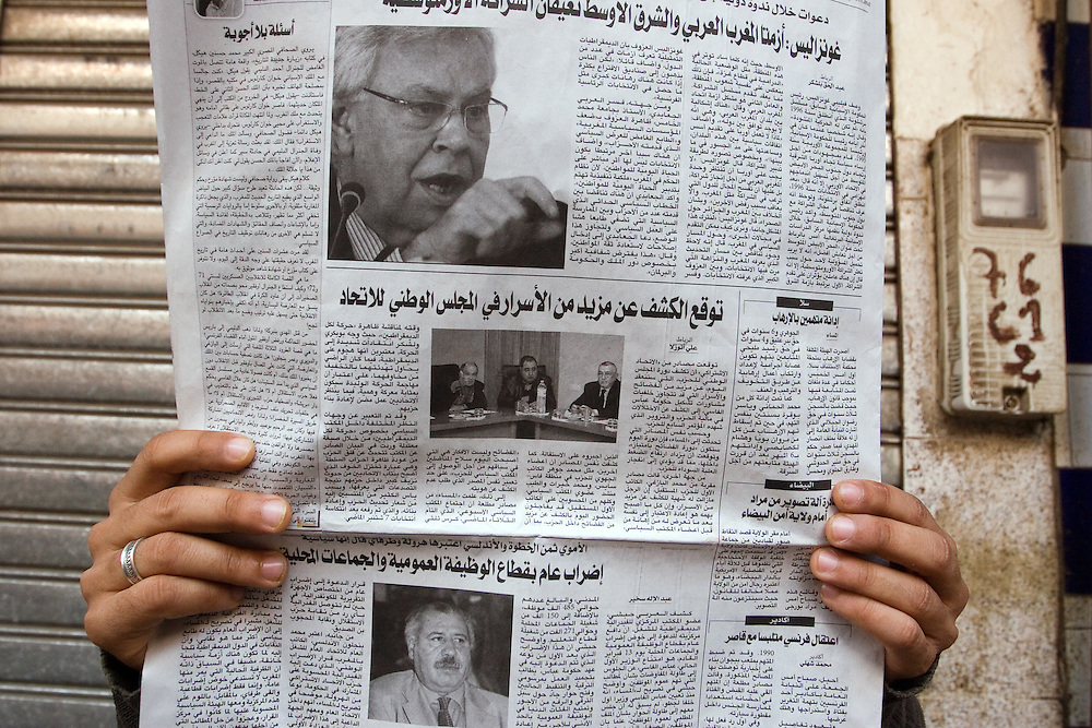 A man reads a newspaper on a street of Marrakech, Morocco.