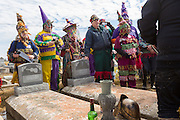 Cajun Mardi Gras revelers gather at the gravesite of legendary fiddler Dennis McGee during the Faquetigue Courir de Mardi Gras chicken run on Fat Tuesday February 17, 2015 in Eunice, Louisiana. The musicians honor the legend of McGee with a brief ceremony at his tomb yearly.