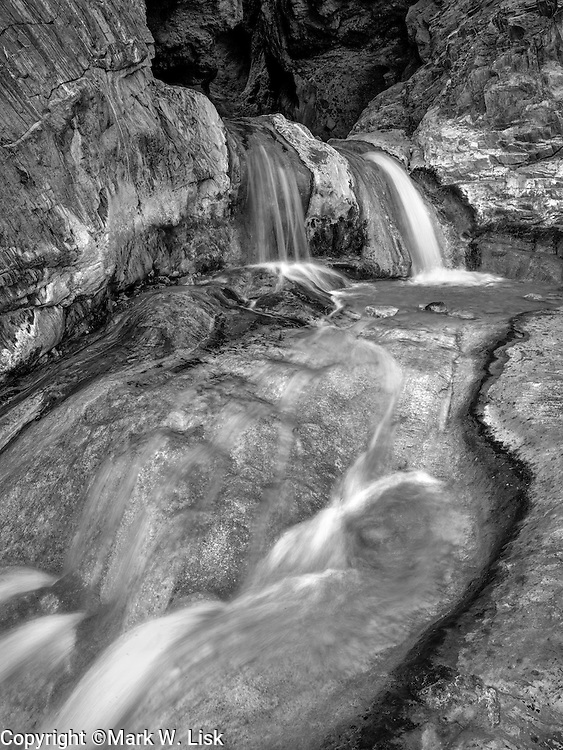 Water spills over travertine shelves of Travertine Canyon in the Lower Granite Gorge of the Grand Canyon.