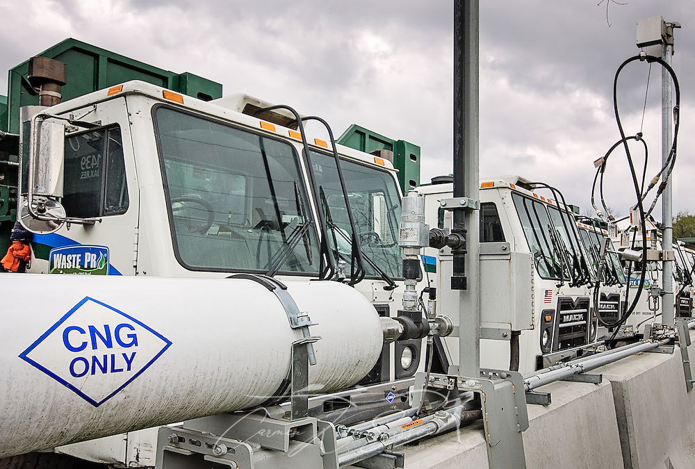 """CNG-powered (compressed natural gas) Mack trucks line up at Waste Pro's time-fill station, March 19, 2016, in Jacksonville, Florida. Waste Pro offers waste and recycling services to more than two million residential customers and more than 40,000 businesses in Alabama, Florida, Georgia, South and North Carolina, Louisiana, Mississippi, and Tennessee. The company has committed to """"going green"""" by implementing a number of green initiatives, including using CNG (compressed natural gas) in its trucks, recycling more waste instead of sending it to landfills, and powering its regional headquarters throuh solar energy. (Photo by Carmen K. Sisson/Cloudybright)"""