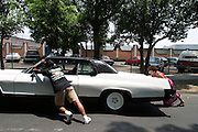 A husband and wife push their broken down car on Mother's Day in Cuernavaca, Morelos, Mexico.