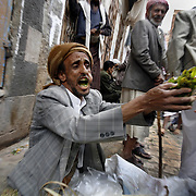 The bustling Qat market in the Central Souq of San'aa. Qat, a leafy narcotic, is almost universally chewed in Yemen. Customers crowd the market around midday in order to purchase their fresh daily supply before retiring to spend the afternoon chewing and socializing.