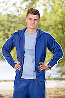 Portrait of smiling fit man standing with hands on hips in park