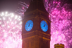 © London News Pictures. 01/01/2016. London, UK. A fireworks display lights up the  skyline behind Big Ben and the Houses of Parliament just after midnight on January 1, 2016 in London, England, to mark the start of 2016. This year the clock face of Big Ben is lit blue as part of the Unicef New Year's Resolution for Children. Photo credit: Ben Cawthra/LNP