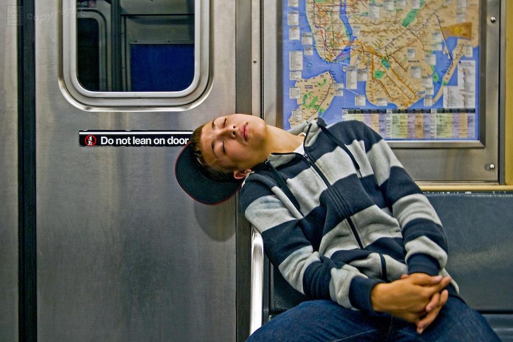 A teenage boy slumps over, sleeping on the New York subway.