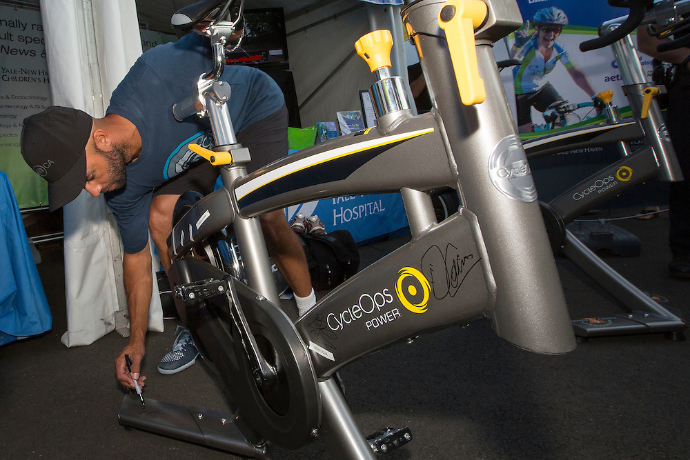 August 20, 2014, New Haven, CT:<br /> James Blake autographs a spin bikes at the Yale New Haven Health booth during the Men's Legends Event on day six of the 2014 Connecticut Open at the Yale University Tennis Center in New Haven, Connecticut Wednesday, August 20, 2014.<br /> (Photo by Billie Weiss/Connecticut Open)