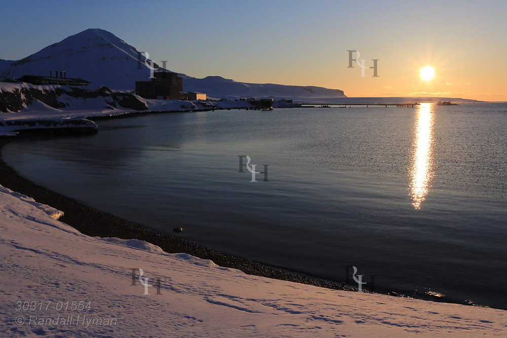 Late evening sun skims along horizon at start of endless summer sunlight in April at the international science village of Ny-Alesund on Spitsbergen island in Kongsfjorden; Svalbard, Norway.