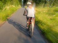 Cyclist biking on trail in Valdez in Southcentral Alaska. Summer. Evening. MR.