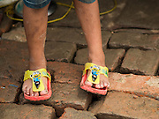 "05 AUGUST 2015 - KATHMANDU, NEPAL:  A child with ""Minions"" flip flops, stands on the brick floor in their tent in a large Internal Displaced Person (IDP) Camp in the center of Kathmandu. The camp is next to one the most expensive international hotels in Kathmandu. More than 7,100 people displaced by the Nepal earthquake in April live in 1,800 tents spread across the space of three football fields. There is no electricity in the camp. International NGOs provide water and dug latrines on the edge of the camp but the domestic waste water, from people doing laundry or dishes, runs between the tents. Most of the ground in the camp is muddy from the running water and frequent rain. Most of the camp's residents come from the mountains in northern Nepal, 8 - 12 hours from Kathmandu. The residents don't get rations or food assistance so every day many of them walk the streets of Kathmandu looking for day work.     PHOTO BY JACK KURTZ"