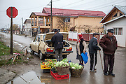 A man is selling vegetables during the Saturday morning market place located at the main road in Marginenii de Jos.