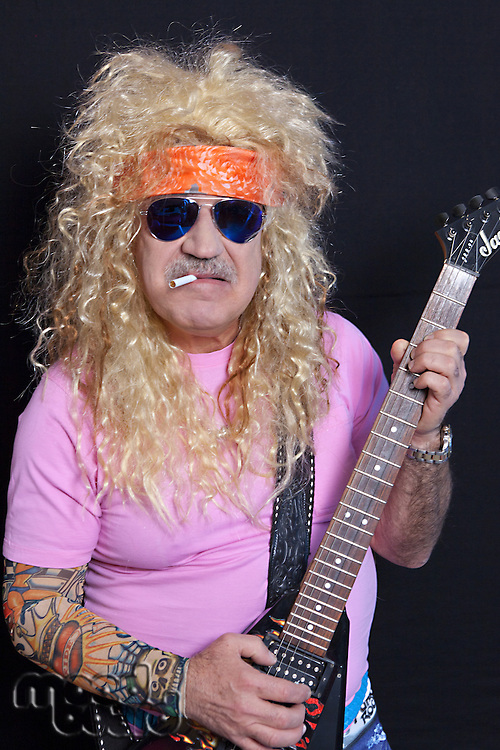 Portrait of middle-aged man wearing sunglasses with guitar smoking cigarette