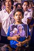 "04 FEBRUARY 2013 - PHNOM PENH, CAMBODIA:  A Cambodian boy holds a portrait of King-Father Norodom Sihanouk during the King-Father's cremation service in Phnom Penh. Norodom Sihanouk (31 October 1922 - 15 October 2012) was the King of Cambodia from 1941 to 1955 and again from 1993 to 2004. He was the effective ruler of Cambodia from 1953 to 1970. After his second abdication in 2004, he was given the honorific of ""The King-Father of Cambodia."" Sihanouk died in Beijing, China, where he was receiving medical care, on Oct. 15, 2012.   PHOTO BY JACK KURTZ"