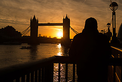 © Licensed to London News Pictures. 03/10/2016. LONDON, UK.  A golden sunrise is seen behind Tower Bridge on the River Thames in London this morning. Sunshine and warm autumn weather are forecast for today.  Photo credit: Vickie Flores/LNP
