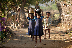 Chitrakoot District, Uttar Pradesh, India: Children carry water on their heads through their small village in the Chitrakoot District of  Uttar Pradesh. In India woman are responsible for carrying out many hard labored tasks. (Photo by Ami Vitale)