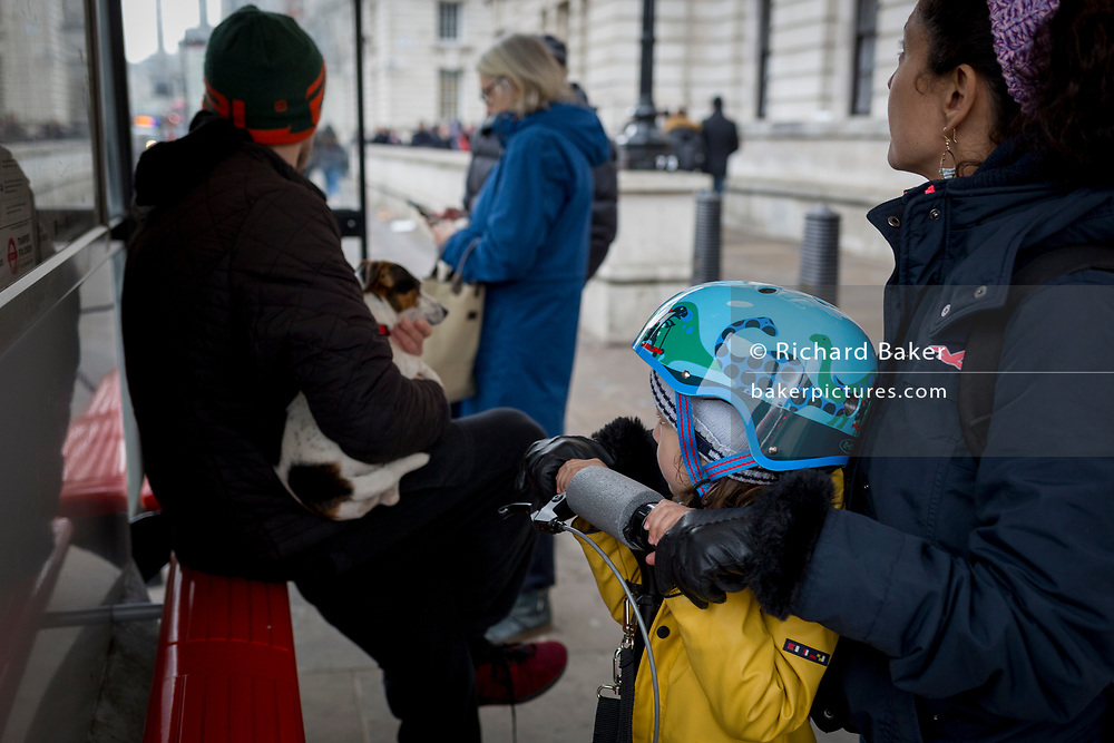 A child holds on to its scooter as a man behind holds his pet terrier at a bus stop in Whitehall, Westminster, on 29th March, 2018 in London, England.
