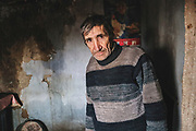 John, a senior in Paicu, Moldova, shows a room in his house damaged by a leaky roof. With no official documents, he is unable to find work to pay for crucial home repairs.