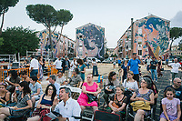 """ROME, ITALY - 27 JUNE 2017: The audience wait fo the premiere of the """"Don Giovanni OperaCamion"""", an open-air opera performed on a truck in San Basilio, a suburb in Rome, Italy, on June 27th 2017.<br /> <br /> Director Fabio Cherstich's idae of an """"opera truck"""" was conceived as a way of bringing the musical theatre to a new, mixed, non elitist public, and have it perceived as a moment of cultural sharing, intelligent entertainment and no longer as an inaccessible and costly event. The truck becomes a stage that goes from square to square with its orchestra and its company of singers in Rome. <br /> <br /> """"Don Giovanni Opera Camion"""", after """"Don Giovanni"""" by Wolfgang Amadeus Mozart is a new production by the Teatro dell'Opera di Roma, conceived and directed by Fabio Cherstich. Set, videos and costumes by Gianluigi Toccafondo. The Youth Orchestra of the Teatro dell'Opera di Roma is conducted by Carlo Donadio."""
