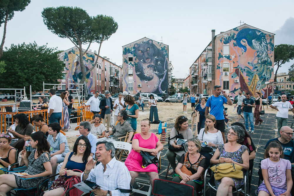ROME, ITALY - 27 JUNE 2017: The audience wait fo the premiere of the &quot;Don Giovanni OperaCamion&quot;, an open-air opera performed on a truck in San Basilio, a suburb in Rome, Italy, on June 27th 2017.<br /> <br /> Director Fabio Cherstich&rsquo;s idae of an &ldquo;opera truck&rdquo; was conceived as a way of bringing the musical theatre to a new, mixed, non elitist public, and have it perceived as a moment of cultural sharing, intelligent entertainment and no longer as an inaccessible and costly event. The truck becomes a stage that goes from square to square with its orchestra and its company of singers in Rome. <br /> <br /> &ldquo;Don Giovanni Opera Camion&rdquo;, after &ldquo;Don Giovanni&rdquo; by Wolfgang Amadeus Mozart is a new production by the Teatro dell&rsquo;Opera di Roma, conceived and directed by Fabio Cherstich. Set, videos and costumes by Gianluigi Toccafondo. The Youth Orchestra of the Teatro dell&rsquo;Opera di Roma is conducted by Carlo Donadio.