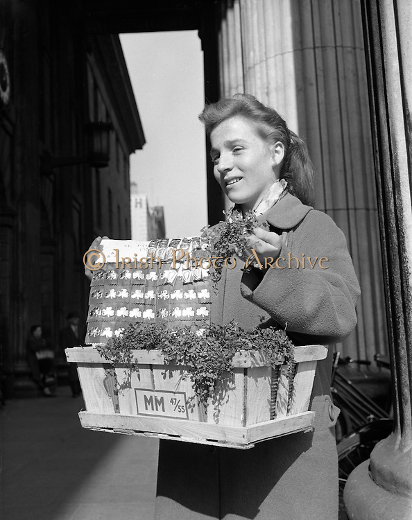 Anyone for a badge or spray of shamrock? Young Girl selling Shamrock   at the GPO, General Post Office, O'Connell Street Lower, Dublin, Ireland. 17.03.1961.<br />