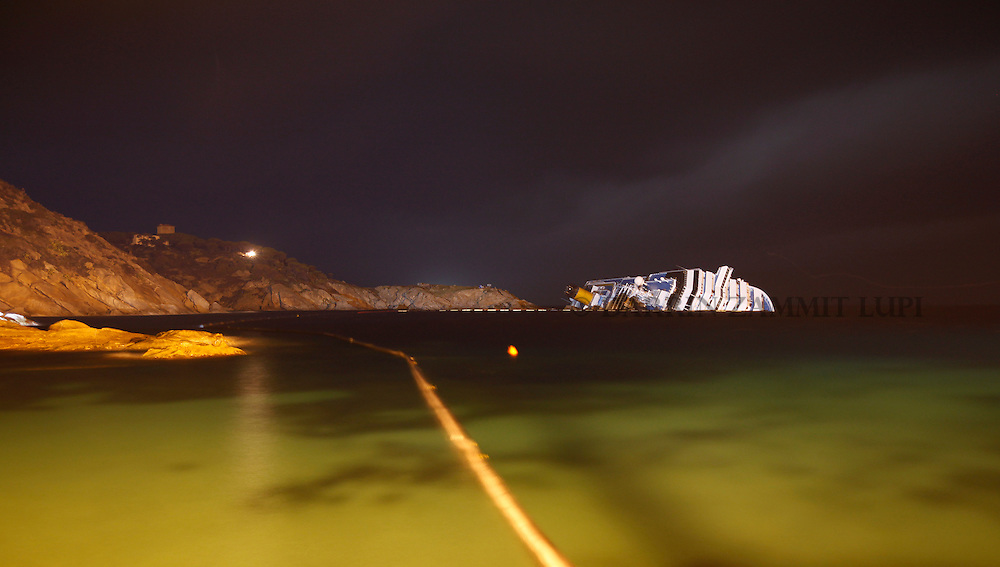 The cruise liner Costa Concordia is seen at night off the west coast of Italy at Giglio island January 31, 2012.  Italian authorities have ended the search for bodies on the submerged sections of the ship, more than two weeks after the giant cruise liner capsized off the Tuscan coast, officials said on Tuesday.  Picture taken with long exposure...REUTERS/Darrin Zammit Lupi (ITALY)