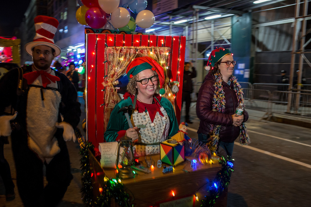 "New York, NY - 31 October 2015. A woman dressed as an elf in Santa's workshop, complete with workbench, tools and toys, at the start of the annual Greenwich Village Halloween Parade. Her name tag reads ""Sparkle Twinklebaum."""