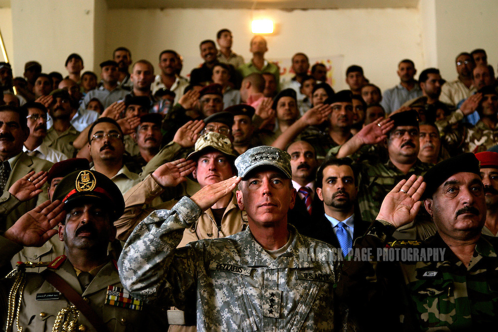 IRAQ, BAGHDAD - JULY 14: General David Petraeus (C), Commander of Multi National Forces (MNF) in Iraq, salutes Iraqi soldiers during an Iraqi Armed Forces officer graduation ceremony at the Rustamiyah Military Academy, July 14, 2008 on the outskirts of Baghdad, Iraq. Having joined in the midst of Iraq's civil war last year, 232 new army and air force lieutenants graduated from the military academy. The academy, founded by the British in 1924, was destroyed and looted after the fall of Baghdad before being reopened by the US-led coalition in 2005. Rebuilding the Iraqi army has been a major challenge for coalition forces since the Coalition Provisional Authority and Bush Administration disbanded it in 2003. The total number of Iraqi Security Forces (ISF), which includes military and police, numbers almost 600,000 personnel and is expected to take control of primary combat responsibilities by mid-2009. Since early 2008, Iraq's security situation has improved with oil production increasing, record government surplus and easing sectarian tensions. (Photo by Warrick Page)