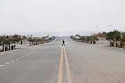 A lone pedestrian crosses an abandoned road in Huinong Qu a new city in northern Ningxia province.
