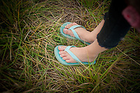 A young girl wearing flip flops in the grass