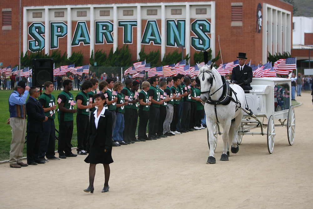 "TORRANCE, CA - JUNE 1: Members of the South High football team bow their heads to the horse-drawn carriage bringing the casket of Cpl. Joseph Anzack, Jr. to his funeral service at South High School where he graduated in 2005 on June 1, 2007 in Torrance, California. Anzack went missing with two other soldiers when their combat team was ambushed on May 12 near Mahmoudiya, south of Baghdad, Iraq. Al Qaeda claimed responsibility for the attack which killed four other U.S. soldiers and an Iraqi interpreter. Two American soldiers remain missing. Earlier this year, his family breathed a sigh of relief after learning that the rumors of his death which prompted South High School students to post a message on the school marquee reading, ""In Loving Memory - Joseph Anzack - Class of 2005"", turned out to be false. Anzack will be interred at Arlington National Cemetery."