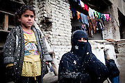 Afghanistan: 28 year old Palwasha with her daughter on the steps on her home,  a dilapidated warehouse building known as Tamil Mill Bus site, owned by the Ministry of Transportation...A wife and mother of 3 boys and 3 girls, she says her husbands daily wage, as a daily labourer of 100Afs (US$2.30) per day is not sufficient for feeding her family. She says her husband leaves the family home at 07.00am every morning returning after nightfall...Her husband occasionally buys  a bulk lot of plastic bags for 10Afs,  which are then divided and sold individually for 5 Afs each by her sons in Kabul city centre. ..Palwasha says she and her family returned from Iran some 7 years ago after fleeing heavy flighting in Kabul in late 1998...She says she sometimes receives help from NHO's such as UNHCR, supplying charcoal during the winter months and NFI's...Afghans returning from exile abroad face many challenges. Security is a major obstacle to return in many districts. Others choose not to return tot heir villages because of landlessness or the lack of job opportunities, fuelling population movements and especially further urbanisation. Impoverished returnees and IDP's living in Kabul cit struggle to meet their daily needs. The attraction of daily wage labour draws growing numbers to the city. But the rising cost of rental accommodation and basic commodities price them out of the market and relegate them to life in the informal settlements which have mushroomed across the city...While 70-80% of kabul city os considered as 'informal' in the sense it is not covered by the Kabul Master Plan, UNHCR's focus is on a limited number of highly documented such 30 sites dotting the city which are home to over 2,000 families. Some families are living under canvas and the constant threat of eviction. others have gained a toe-hold in abandoned around building in the city...Afghanistan/UNHCR/Jason Tanner/February 2011