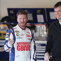 NASCAR Sprint Cup driver Dale Earnhardt Jr. jokes with a member of his team in the garage area, during a NASCAR Daytona 500 practice session at Daytona International Speedway on Wednesday, February 20, 2013 in Daytona Beach, Florida.  (AP Photo/Alex Menendez)