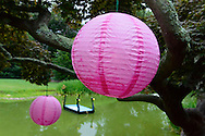 Old Westbury, New York, USA. 28th June 2015. Colorful pink round lanterns, hanging from trees around the pond, decorate the grounds of historic Old Westbury Gardens, a Long Island Gold Coast estate, during its Midsummer Night event.