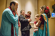 Baltimore, Maryland - December 20, 2014: The flower girls at Trisha Satya Pasricha and Eshwan Ramudu wedding are negotiating a price with the best man for the return of the groom's shoes, which are hidden in their sarees. Shoes are not allowed in the mandap, the traditional Hindu wedding structure, and it is customary after the ceremony for children to ransom the shoes. Karli Khanna-Reichert, 12, from Princeton Junction, NJ, far right, and Olivia Sherwin, 9, from Essex Junction, Vermont, middle right, started negotiations at $1500. Best Man Alex Bick, left, eventually procured the shoes for $150. <br /> <br /> CREDIT: Matt Roth for The New York Times<br /> Assignment ID: 30168620A