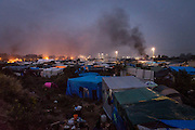 CALAIS, FRANCE - OCT 24: Smoke rises from fires burning inside the 'jungle' camp in Calais, France on October 24, 2016.