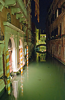 Night view of an elegant gondola dock on a small canal in Venice with lovely reflections on the water.