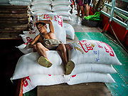 22 NOVEMBER 2017 - YANGON, MYANMAR: A worker sleeps on sacks of rice on a barge docked on the Twante Canal in Yangon. Myanmar's road system lags behind its neighbors in Southeast Asia and a lot of cargo is still moved by ships and barges.    PHOTO BY JACK KURTZ
