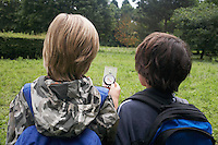 Two boys (7-9) with backpacks using compass back view