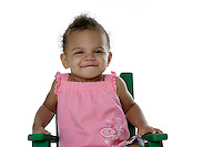 20 July 2008: Adopted little girl a 14 month old bi-racial toddler named Mason Mangus in the studio on a white background sitting in a green chair wearing pink. Silo.