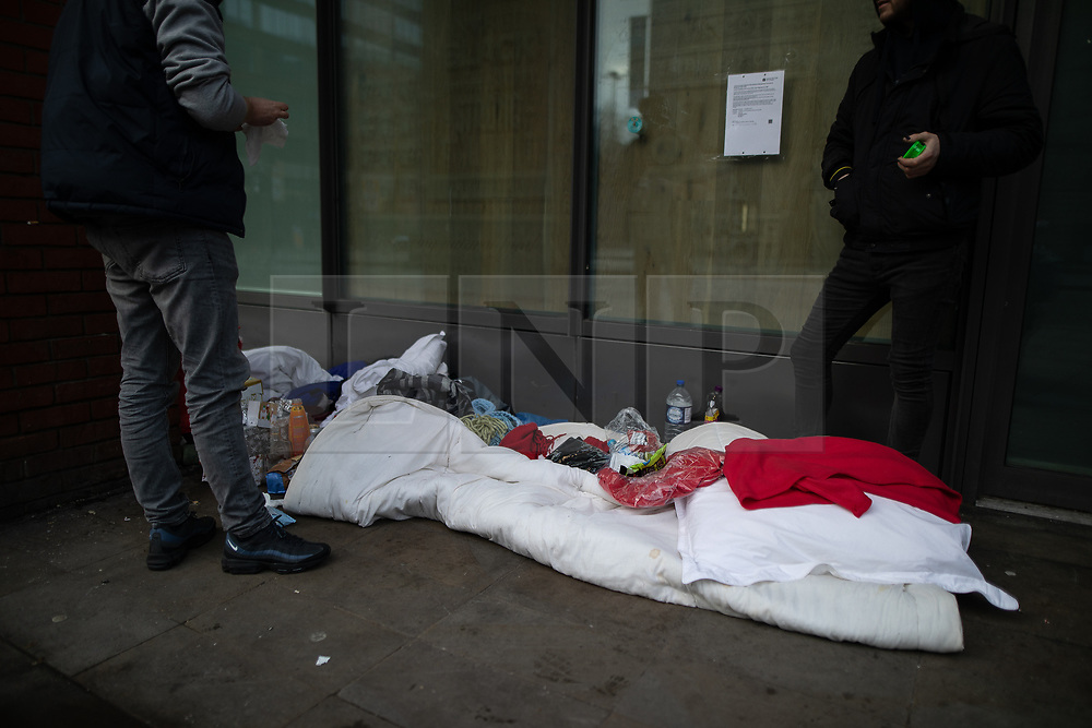 © Licensed to London News Pictures . 25/12/2018 . Manchester , UK . Two homeless people tidy their bedding where they are sleeping rough on Portland Street . Homeless people sleeping rough on the streets of Manchester City Centre on Christmas Day . Photo credit : Joel Goodman/LNP