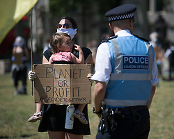 © Licensed to London News Pictures. 30/05/2020. London, UK. Police officers talk to members of the environmental protest group Extinction Rebellion as they take part in a silent protest in Parliament Square calling for a citizens assembly to tackle the threat of COVID-19. Government has announced a series of measures to slowly ease lockdown, which was introduced to fight the spread of the COVID-19 strain of coronavirus. Photo credit: Ben Cawthra/LNP