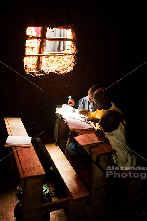 Nairobi, June 2010 -  Boys work at their school work in and on used  unlit mudbrick classroom  at the Saint Catherine children's home in Kibera slum.