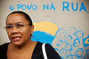 """Jomarina, coordinator at Prestes Maia gives an interview in from of the occupation. The graffiti on the wall says: """"The people on the street"""""""
