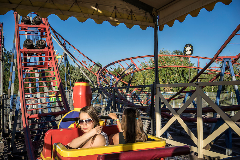 MARIUPOL, UKRAINE - AUGUST 30, 2015: Girls ride a roller coaster at the Mariupol Extreme Park, an amusement park in Mariupol, Ukraine. Despite the front line being a relatively short distance away, Mariupol was lively on a warm summer weekend, with little evidence that people expect the fighting to advance this far. CREDIT: Brendan Hoffman for The New York Times