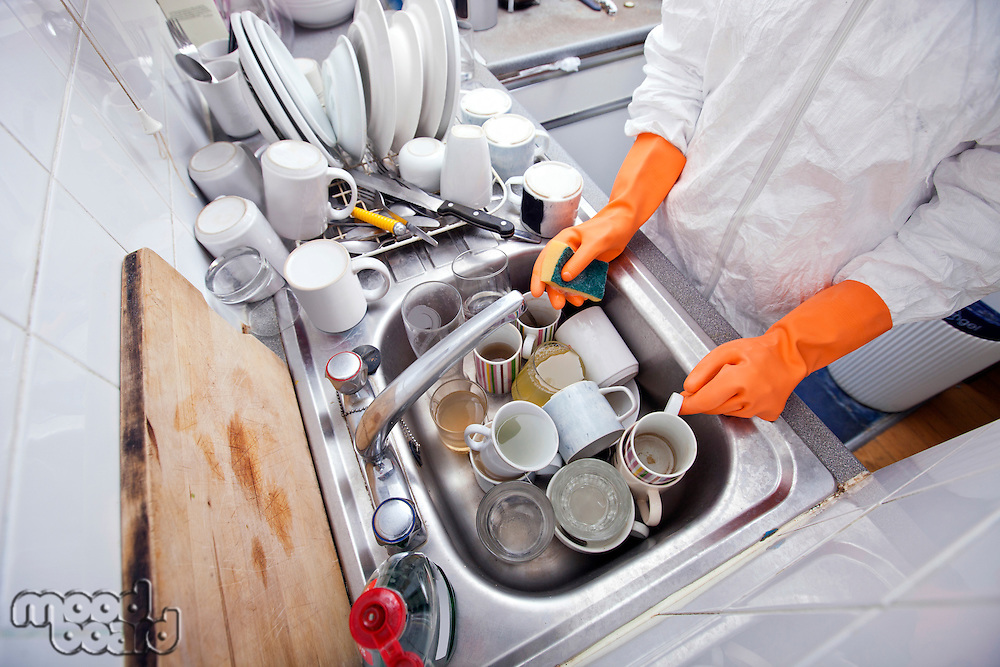 Midsection of woman washing utensil at kitchen sink