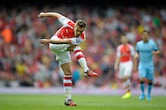 Arsenal's Aaron Ramsey taking a shot. Barclays Premier league match, Arsenal v Manchester city at the Emirates Stadium in London on Saturday 13th Sept 2014.<br /> pic by John Patrick Fletcher, Andrew Orchard sports photography.