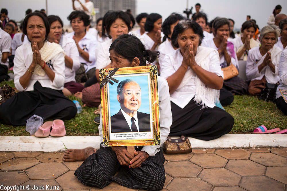 02 FEBRUARY 2013 - PHNOM PENH, CAMBODIA:  Women pray on the sidewalk along Sisowath Quay, Phnom Penh's riverfront boulevard. Much of Phnom Penh has been shut down to honor former King Norodom Sihanouk, who ruled Cambodia from independence in 1953 until he was overthrown by a military coup in 1970. Only bars, restaurants and hotels that cater to foreign tourists are supposed to be open. The only music being played publicly is classical Khmer music. Sihanouk died in Beijing, China, in October 2012 and will be cremated during a state funeral royal ceremony on Monday, Feb. 4.    PHOTO BY JACK KURTZ