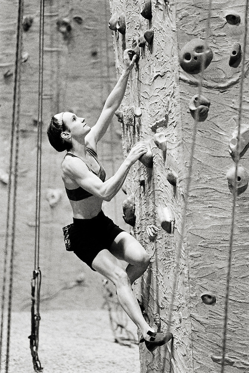 A young fit woman climbing at an indoor climbing gym.